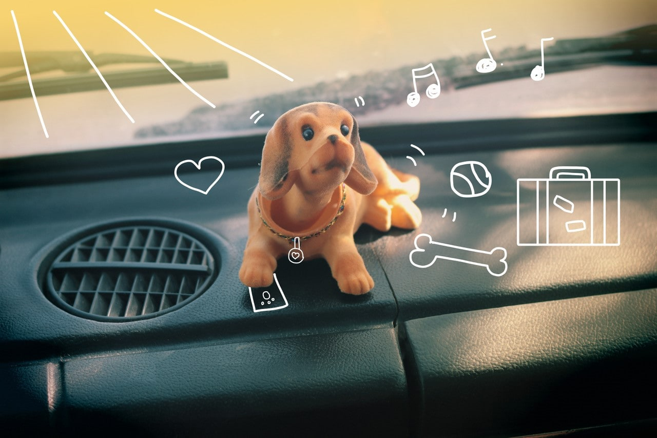 Nodding toy dog on a car dashboard. Pet insurance from MiPet Cover.